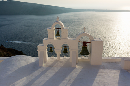 Arch with cross and bells of traditional Greek white church in Oia village, Santorini Island, Greece