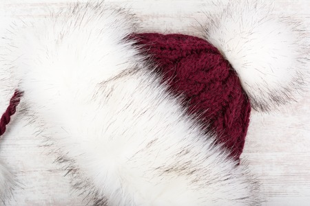 Red knitted winter hat with fur on white wooden background Stock Photo