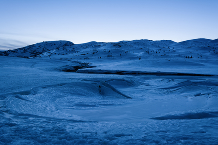 Winter mountain landscape. Frozen lake covered with snow and ice at blue hour. Dam Belmeken in winter, Bulgaria