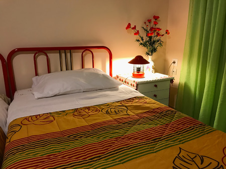 Vibrant Colored Interior of a bedroom. Pillow and colorful coverlet on the bed. Bedroom interior design Stock Photo