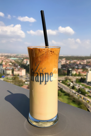Ice frappe coffee and view of town of Sofia for background