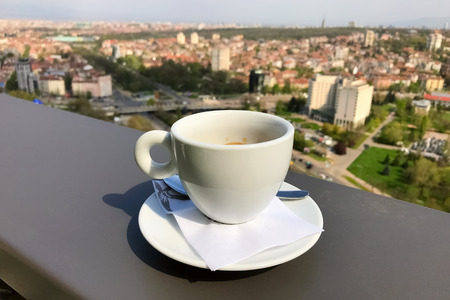 Espresso coffee and view of town of Sofia for background