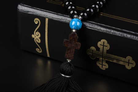 Closeup of Holy Bible and rosary beads with cross on black background. Religion concept and faith