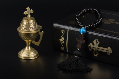 Closeup of Holy Bible, rosary beads with cross and incense burner on black background. Religion concept and faith