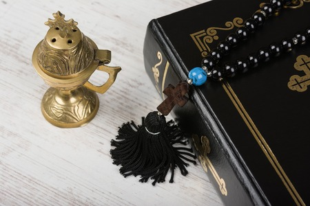 Closeup of Holy Bible, rosary beads with cross and incense burner on white wooden background. Religion concept and faith.
