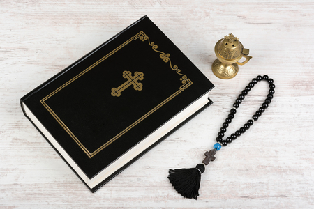 Holy Bible, rosary beads with cross and incense burner on white wooden background. Religion concept and faith.