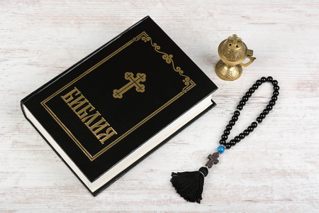 BURGAS, BULGARIA - MARCH 22, 2019: Holy Bible, rosary beads with cross and incense burner on white wooden background. Religion concept and faith. Cyrillic text means Bible in bulgarian and russian. Stock Photo
