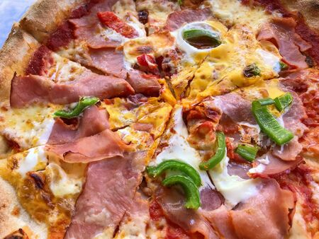 Pizza with ham, bacon, tomatoes, onion eggs and pepper.