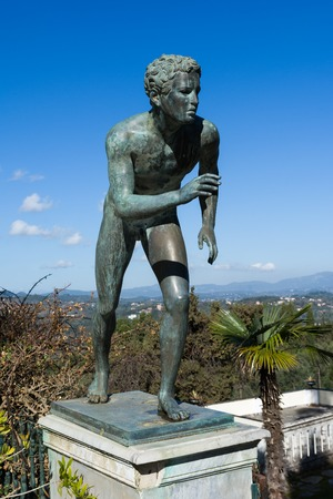 CORFU, GREECE - MARCH 4, 2017: A statue of The Runner in the garden of Achilleion palace in Corfu Island, Greece, built by Empress of Austria Elisabeth of Bavaria, also known as Sisi.