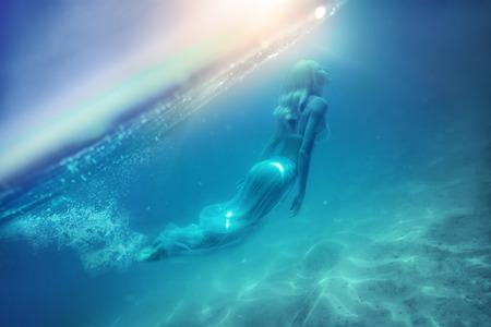 The beautiful girl dives in the ocean. Nalaguraidhu (Sun Island Resort). Southern Ari Atoll. Maldives