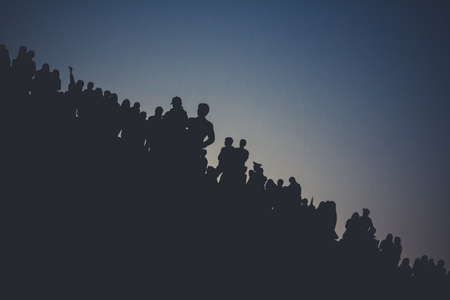 Russia, Moscow -  Spring 2007: Mass celebrations in the city. Silhouettes of people on a hill at sunset