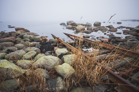 Stony coast of the Baltic Sea. Rails for launching ships into the water. Foggy spring morning. Leppneeme sadam. Estonia