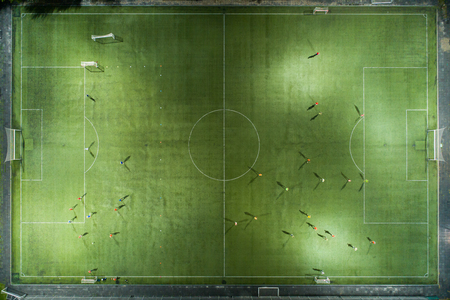 Football players running around the football field. Night workout. Preparation for the match.  Aerial shot with a drone from a altitude Фото со стока - 88071673