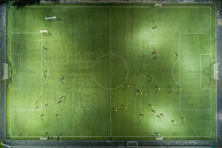Jugadores de fútbol corriendo por el campo de fútbol. Entrenamiento nocturno. Preparación para el partido. Toma aérea con un dron desde una altitud