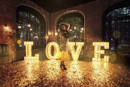 Beautiful girl posing against a background of shining letters. From the letters the word love is composed. Golden petals are scattered on the floor. Loft with large windows. Stok Fotoğraf