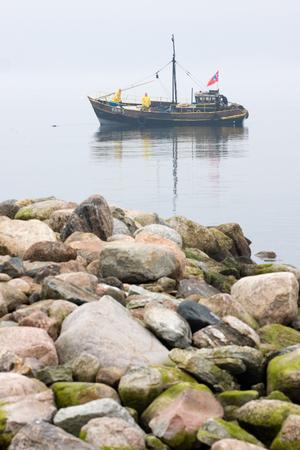 Fishermen on the boat in the Baltic Sea. Foggy spring morning. Leppneeme sadam. Estonia