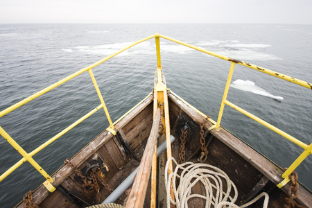 rapprochement: Foggy spring morning. The fishing ship is moving toward the ice floe. View from the bow of the ship. Baltic Sea. Estonia. Stock Photo