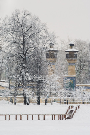 Snow-covered park in winter. Against the background, you can see a minaret and a fresco on the arch at the entrance to the mosque. Moscow. Russia Stok Fotoğraf