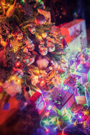 Gifts and Christmas decorations next to a glowing Christmas tree