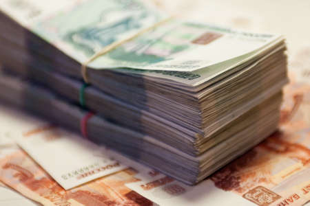 A bundle of banknotes on the background of other banknotes. 1000 and 5000 rubles