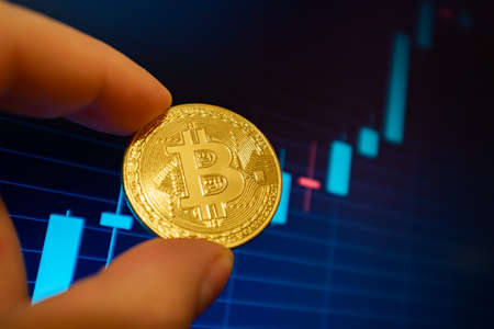 Bitcoin cryptocurrency coin on the background of the exchange chart
