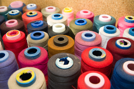 machinist: Many reels of colored threads standing on the table Stock Photo