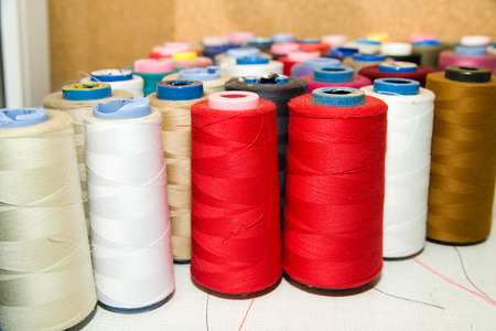 modiste: Many reels of colored threads standing on the table Stock Photo