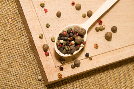 repast: Wooden spoon filled with a mixture of grains of pepper are on a wooden surface Stock Photo