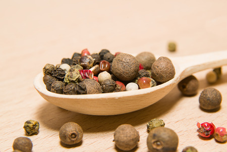 piquancy: Wooden spoon filled with a mixture of grains of pepper are on a wooden surface Stock Photo