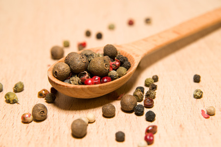 smack: Wooden spoon filled with a mixture of grains of pepper are on a wooden surface Stock Photo