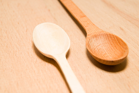 repast: Two wooden spoons of different colors are on the surface Stock Photo