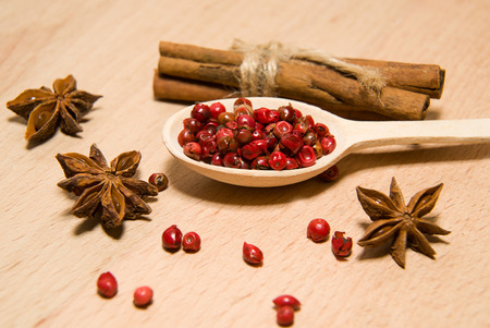 savour: wooden Spoon with a mixture of grains of pepper, cinnamon and star anise on a wooden surface Stock Photo