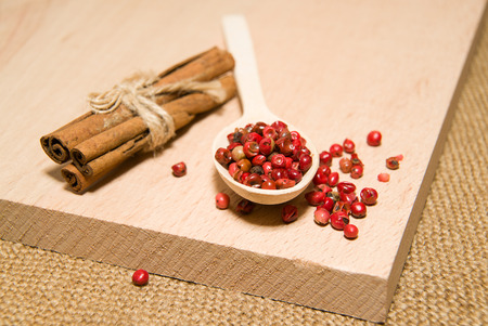 repast: wooden Spoon with a mixture of grains of pepper and cinnamonon a wooden surface