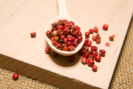 savour: Wooden spoon filled with a mixture of grains of pepper are on a wooden surface Stock Photo