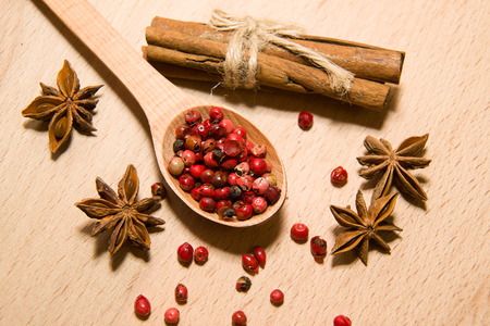 repast: wooden Spoon with a mixture of grains of pepper, cinnamon and star anise on a wooden surface Stock Photo