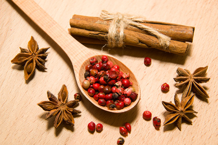 piquancy: wooden Spoon with a mixture of grains of pepper, cinnamon and star anise on a wooden surface Stock Photo