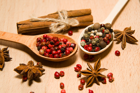 ligneous: wooden Spoons with a mixture of grains of pepper, cinnamon and star anise on a wooden surface