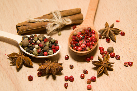 savour: wooden Spoons with a mixture of grains of pepper, cinnamon and star anise on a wooden surface