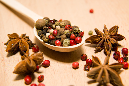 piquancy: Wooden spoon filled with a mixture of grains of pepper and star anise on a wooden surface Stock Photo