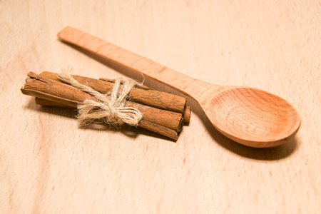 smack: wooden Spoon and cinnamon  on a wooden surface Stock Photo