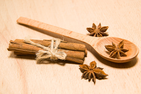 smack: wooden Spoon, cinnamon and star anise on a wooden surface