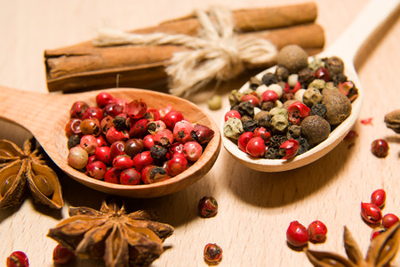 piquancy: wooden Spoons with a mixture of grains of pepper, cinnamon and star anise on a wooden surface