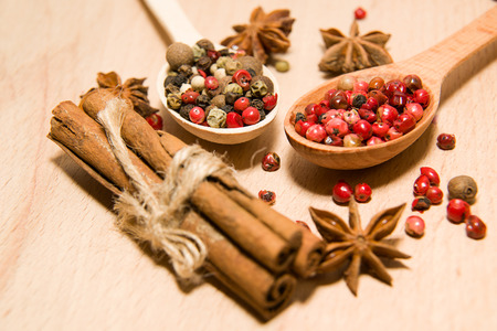 smack: wooden Spoons with a mixture of grains of pepper, cinnamon and star anise on a wooden surface