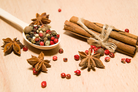 smack: wooden Spoon with a mixture of grains of pepper, cinnamon and star anise on a wooden surface Stock Photo