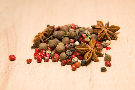 piquancy: mixture of grains of pepper and star anise on a wooden surface