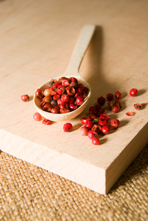 piquancy: Wooden spoon filled with grains of pepper  on a wooden surface Stock Photo