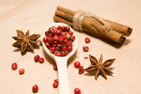 repast: wooden Spoon, grains of pepper, cinnamon and star anise on a wooden surface
