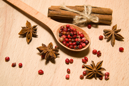 ligneous: wooden Spoon, grains of pepper, cinnamon and star anise on a wooden surface