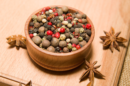 poignant: A mixture of grains of pepper and star anise on a wooden surface