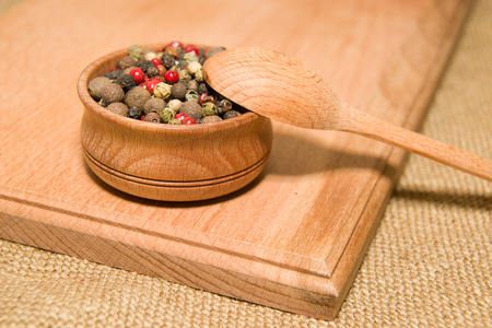 odorous: A mixture of grains of pepper and spoon on a wooden surface Stock Photo